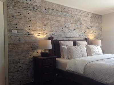 Timber feature walls in a bedroom - Whitewashed Sleeper panels by Northern Rivers Recycled Timber